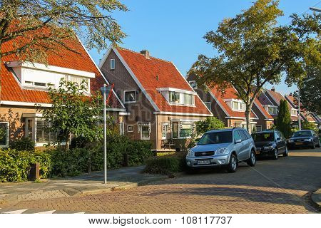 Picturesque Residential Houses And Parked Autos In Small Dutch Town Zwanenburg, The Netherlands