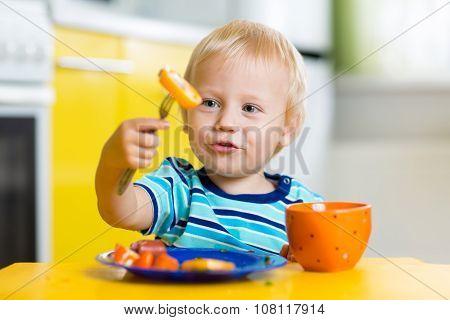 Cute child boy eats healthy food vegetables