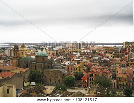 Cagliari's Skyline With Buildings, Port, Sea And Gloomy Grey Cloudy Sky