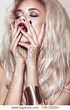 Beautiful sexy blonde girl with sensual lips, fashion hair, black nails and gold accessories. Beauty
