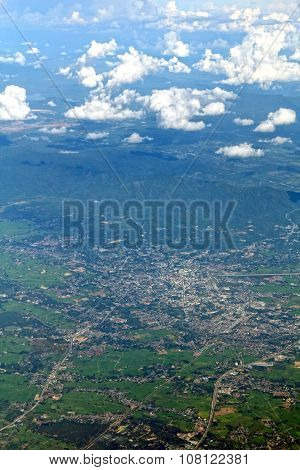 Aerial view of village landscape and mountains over clouds, blur background.