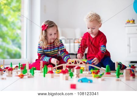 Children Playing With Toy Railroad And Train