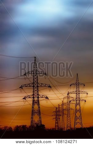colorful sunset and silhouette of electric pillars