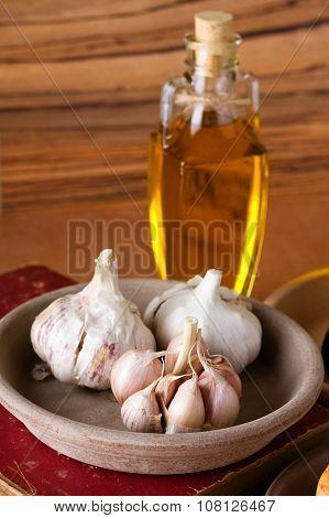 Three Garlic Bulbs In Clay Bowl