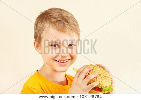 Little smiling boy with tasty hamburger