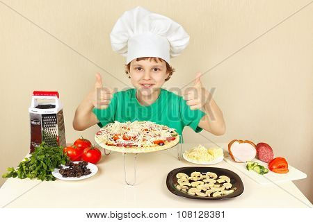 Little boy in chefs hat enjoys cooking pizza