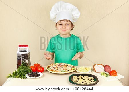 Young smiling chef in chefs hat enjoys cooking tasty pizza