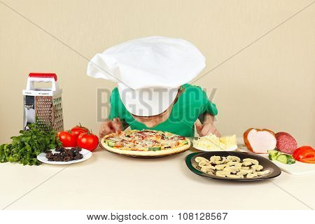 Little funny boy in chefs hat sniffing cooked pizza