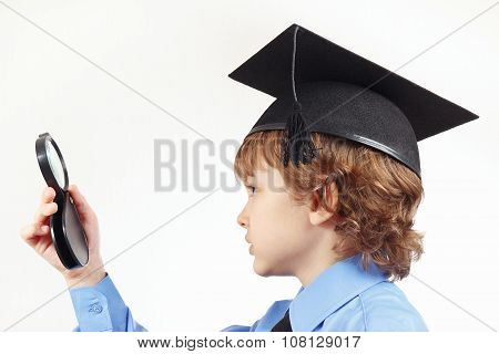 Little pensive boy in academic hat with a magnifying glass on white background