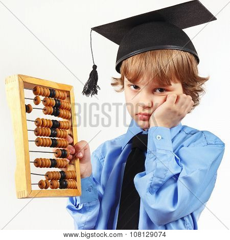 Little tired boy in academic hat with old abacus on white background