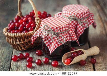 Jars Of Cranberries Jam And Basket With Bog Berry On Background.