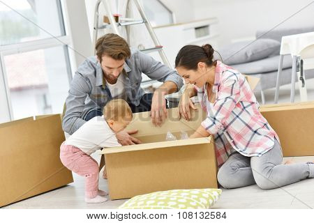 Young family unpacking boxes in new home