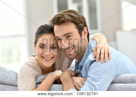 Portrait of couple sitting in sofa at home