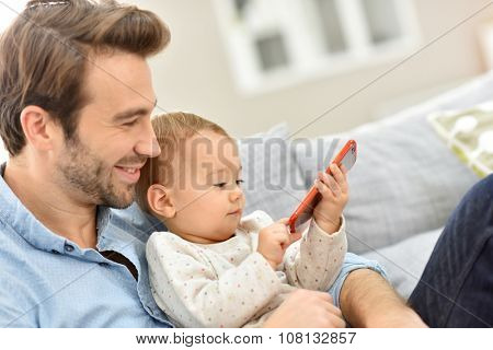 Daddy and baby girl playing with smartphone