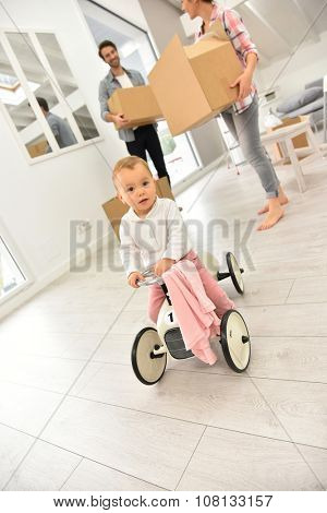 Baby girl playing with child car while family moving in
