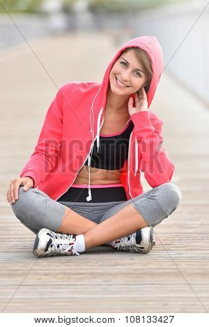 Closeup of young woman in running outfit sitting on floor