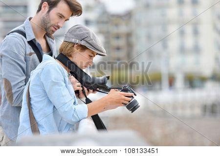Photographers checking photo shots on camera screen
