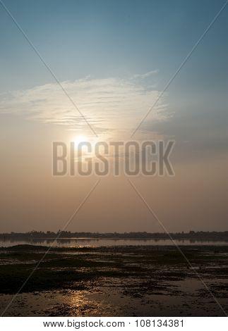 Asian Lake With Water Plants Sunbeams Orange Sun Blue Sky Beautiful Sunset