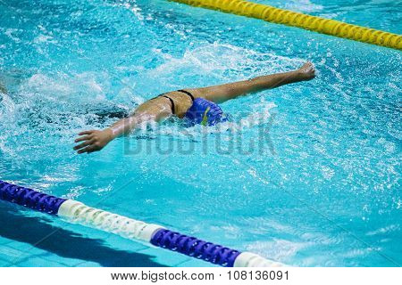 young female athlete swimming butterfly stroke in pool