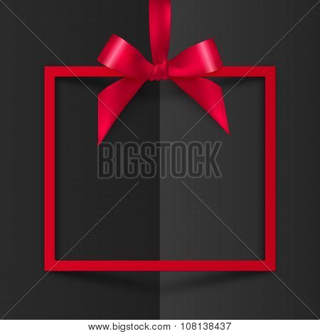 Red gift box frame with silky bow and ribbon on black folded paper background