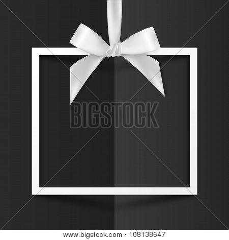 White gift box frame with silky bow on black folded paper background