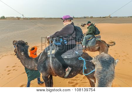 MERZOUGA, MOROCCO, APRIL 13, 2015: Senior tourists take part in camels trip on sand dunes of Erg Chebbi