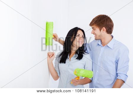 young couple paint at home wall