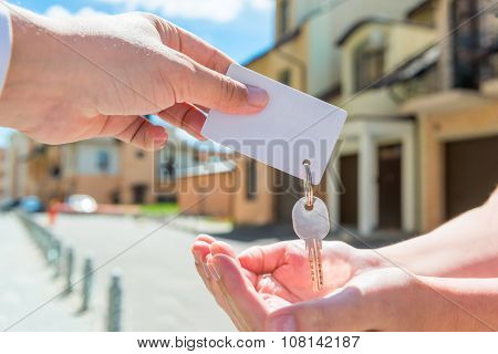 Key Of Apartment And A Card For An Inscription In The Hands Of People
