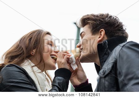 Couple Eating Hotdog Together Against Sky