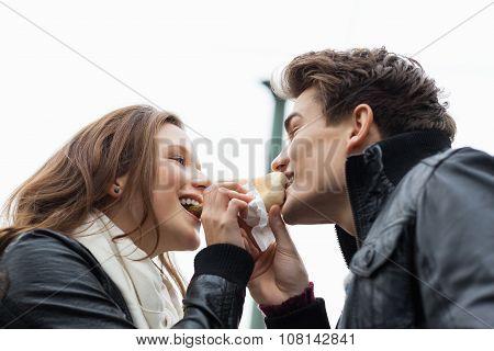 Couple Eating Hotdog Together Against Sky