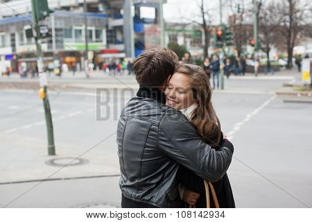 Couple In Jackets Embracing On Street Side