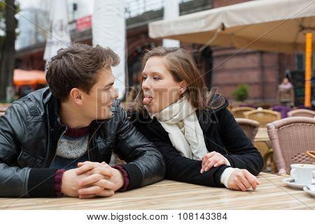 Woman Teasing Man While Sitting At Outdoor Restaurant