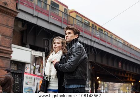Couple Looking Away Against Train Bridge