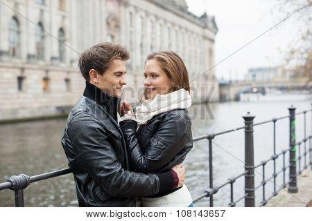 Romantic Couple In Jackets Embracing By Railing