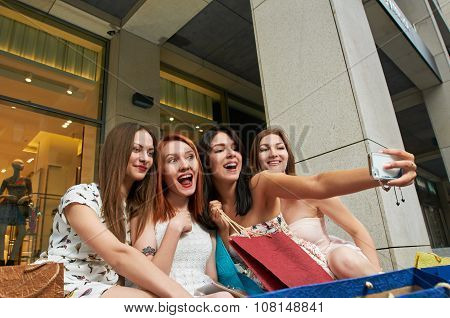 four young women shopping at the mall taking a selfie