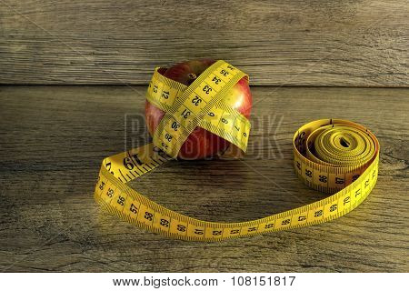 Measuring tape with a red apple