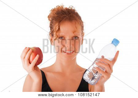 Young female holding red apple and plastic bottle of water