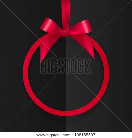 Red round frame with silky bow and ribbon at black folded paper background