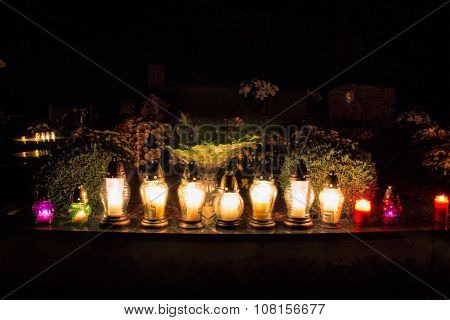 All Saints Day. Candles burning on graves at a cemetery at night. All Hallows Eve / Day of All the S