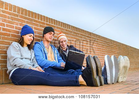 Friends Relaxing And Chilling With Laptop In Campus - Tecnology, University And Friendship Concept -