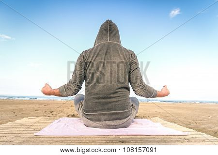 Young Man Meditating On The Beach At Beginning Of Autumn - Meditation Concept In Nature Quiet Locati