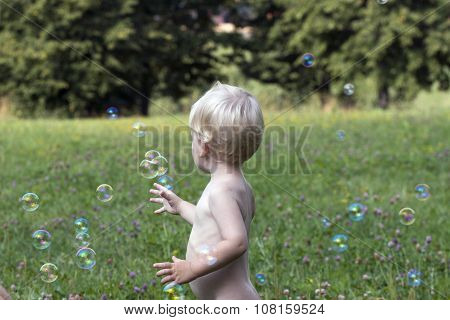 Baby boy play with soap bubbles