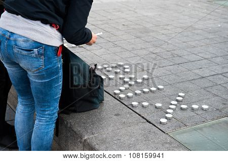 STRASBOURG FRANCE - 14 NOV 2015: Light candles near General Kleber statue in tribute to the victims of the terrorist attacks in Paris - people writing PEACE word with candles