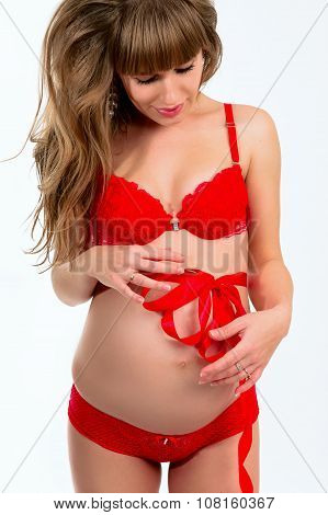 Portrait of beautiful pregnant young woman in red lingerie on a light background.