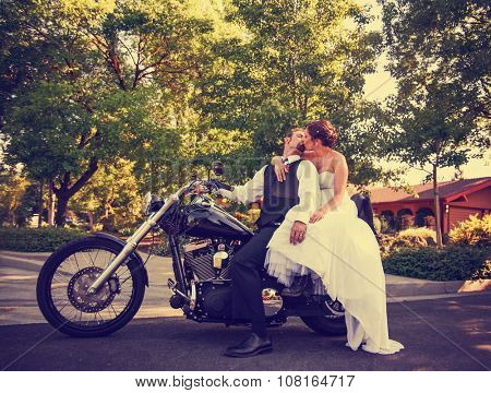 a couple on their wedding day on a black motorcycle in an urban neighborhood toned with a retro vintage instagram filter app or action effect