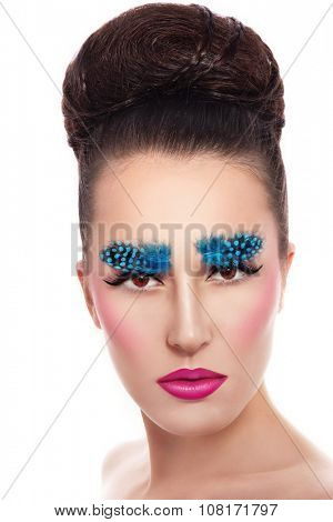Young beautiful woman with fancy feather eyebrows, ombre lips and stylish hair bun over white background