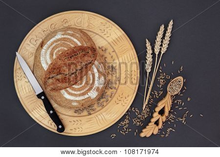 Homemade rye bread loaf on a wooden board with knife, grain and wheat sheaths with carved lovespoon on grey background.