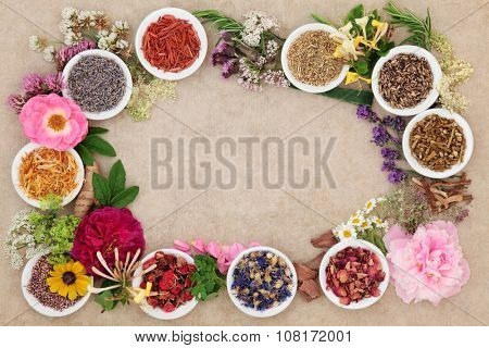 Herbal medicine flower and herb selection forming an abstract background  border over handmade hemp paper background.