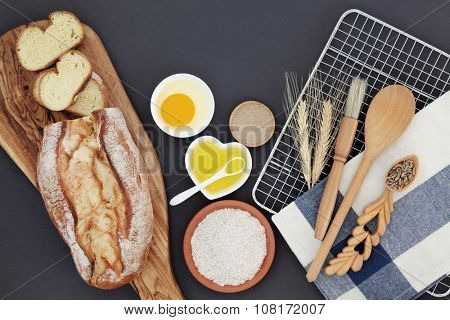French bread loaf with baking ingredients and utensils with wheat sheaths and grain in a lovespoon on grey  background.