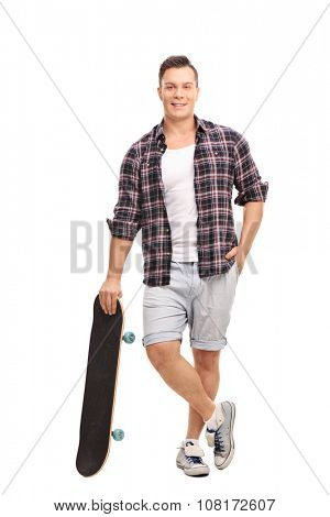 Full length portrait of a young male skater leaning on his skateboard and looking at the camera isolated on white background